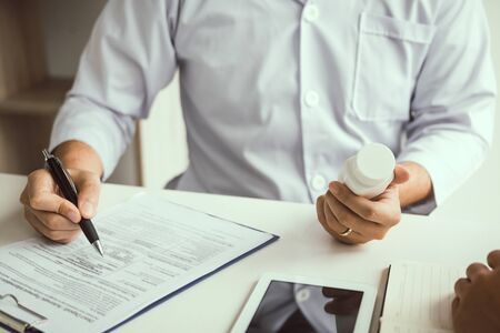 Confident doctor man holding a pill bottle and writing while talking with senior patient and reviewing his medication at office room.
