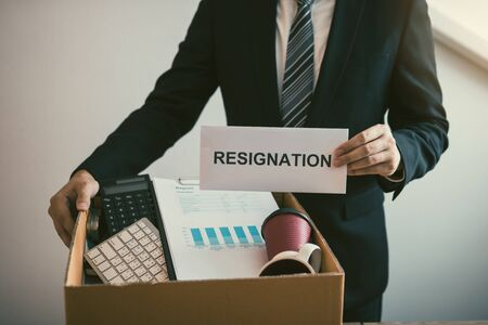 Male employees are keeping their own items on the desk because they are about to go to resign with the manager.