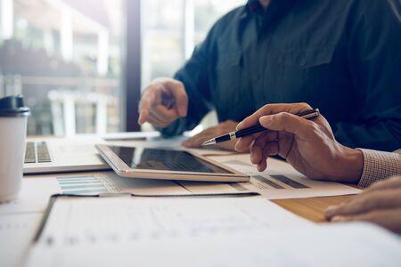 Geschäftspartner von Geschäftspartnern analysieren den Arbeitsfortschritt der Kosten und verwenden ein Tablet, um den Finanzbudgetbericht des Unternehmens und die Planung für die Zukunft im Büroraum grafisch darzustellen.