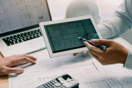 Zwei Ingenieure arbeiten zusammen und verwenden ein digitales Tablet mit Blaupause und Analyse mit Architekturplan auf dem Schreibtisch.