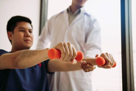 Asian young male physiotherapist helping patient with lifting dumbbells exercises in office.