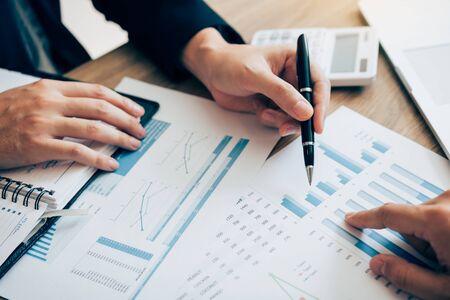 회사의 회계 직원이 사무실 책상에 있는 비용 그래프를 공동으로 분석하고 있습니다.