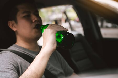 Asian men are breaking the traffic rules by holding a bottle of beer and drinking while driving. Imagens