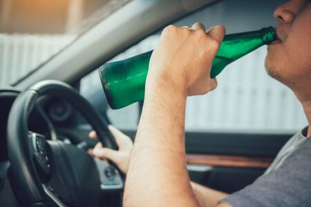 Asian men are breaking the traffic rules by holding a bottle of beer and drinking while driving. 免版税图像