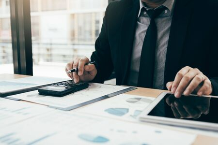 Businessmen are using calculators to calculate the company profit by deducting from expenses and using tablets to find information data on table in office room. Imagens