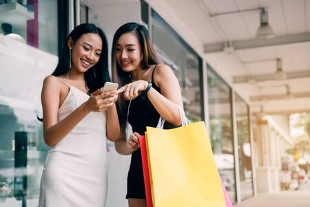 Two asian woman standing at store front with happy watching smart phone at shopping mall center. Imagens