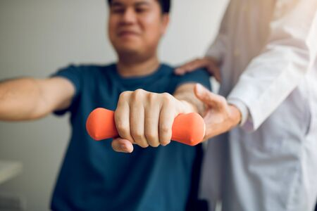 Asian physiotherapist helping a patient lifting dumbbells work through his recovery with weights in clinic room. Banque d'images