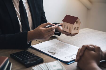Business people home sales broker is using a pen pointing to the house model and describing the various components of the house.