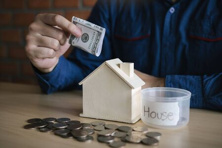 Men are using banknotes in the home piggy bank with the idea of collecting money to buy a new house. Stockfoto