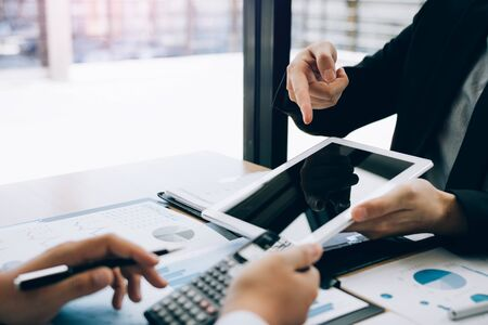 Managers are using tablets to analyze sales cost reports and explain summary reports to employees calculate and record summary information data in the office. 스톡 콘텐츠