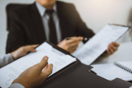Der Mitarbeiter beschreibt die Berufserfahrung im Lebenslaufpapier für den Manager im Büro.