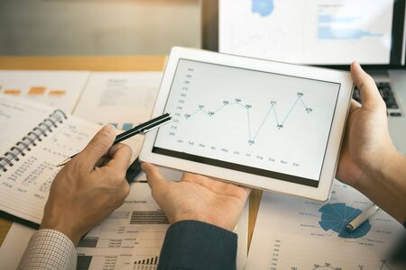 Business partnership coworkers analysis cost work progress and using a tablet to graph company financial budget report and planning for future in office room. 版權商用圖片