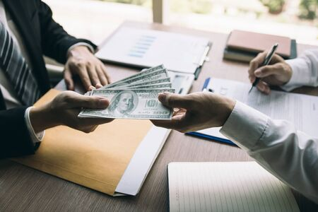 Entrepreneurs are about to sign a contract that allows partners to file cash for bribes. Stockfoto