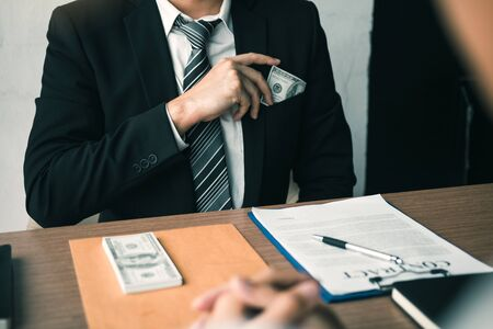 Businessman putting stack of money bills in his suit coat pocket. Stock fotó