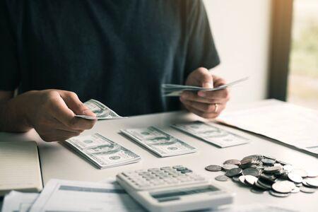 Los hombres asiáticos sostienen billetes en efectivo y los colocan sobre la mesa con la idea de ahorrar dinero. Foto de archivo