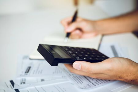 Man use calculators and documents that calculate expenses in the home office.