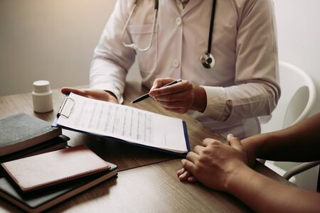 Doctor is writing the appointment letter to the patient at the clinic.