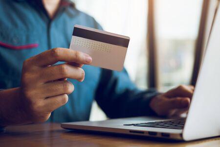 Nahaufnahme Hände des Mannes halten Kreditkarten und mit Laptops Computer betreten Websites, um Produkte zu kaufen.