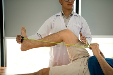 Confident physical therapist helps patient use resistance band stretching out his leg in clinic room.
