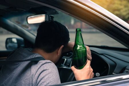 Asian men drink a lot of alcohol until and unconscious his cant drive home and decide to sleep at the steering wheel.