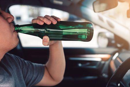 Asian men are breaking the traffic rules by holding a bottle of beer and drinking while driving. Stockfoto