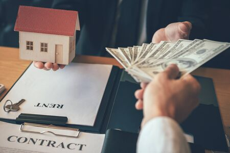 Businessman handed the money new home and real estate trading concepts. Stock fotó