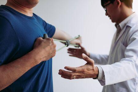 Descenso de fisioterapeuta masculino asiático que trabaja y ayuda a proteger las manos de los pacientes con el paciente haciendo ejercicio de estiramiento con una banda de ejercicio flexible en la sala de la clínica.