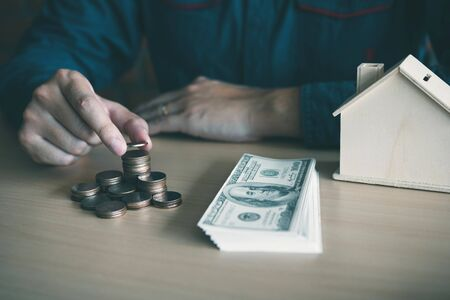 Men are putting coins together with the idea of collecting money to buy a new house.