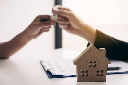 Hand of real estate agent passes the key to new homeowners in office with buyer house concept. Stok Fotoğraf