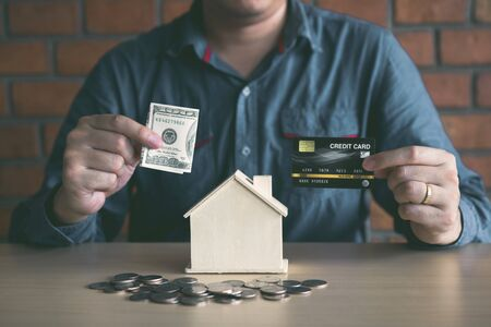 Men are using banknotes in the home piggy bank with the idea of collecting money to buy a new house. 写真素材 - 130110061