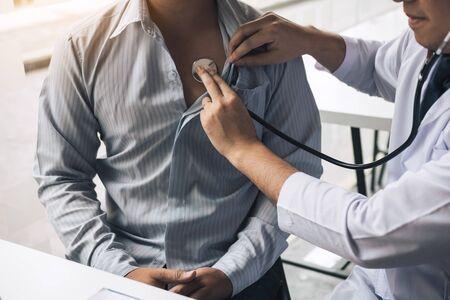 Asiatischer Arzt verwendet ein Stethoskop und hört den Herzschlag des älteren Patienten. Standard-Bild