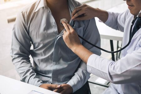 Il medico asiatico sta usando uno stetoscopio per ascoltare il battito cardiaco del paziente anziano. Archivio Fotografico