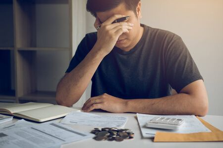 Asian men are stressed about financial problems, with invoices and calculators placed on the table while having stress on problems with home expenses.