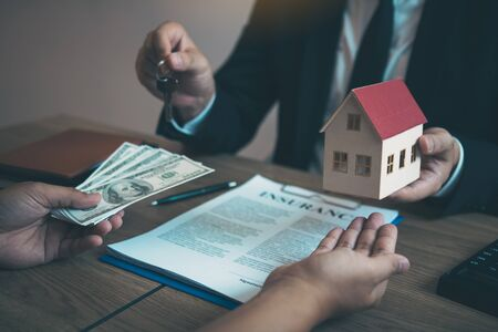 Businessman handed the house model and new homeowner giving money to real estate trading. Stock fotó