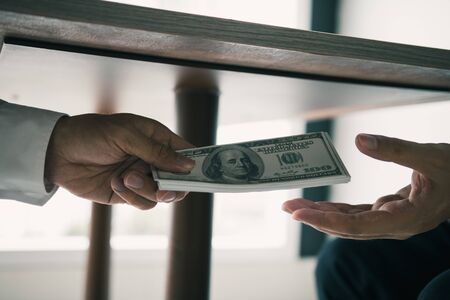 Entrepreneurs are receiving money under the desk that is a bribe of their partners with both of whom are corrupt in the company room.