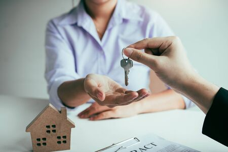 Hand of real estate agent passes the key to new homeowners in office with buyer house concept. Stock fotó