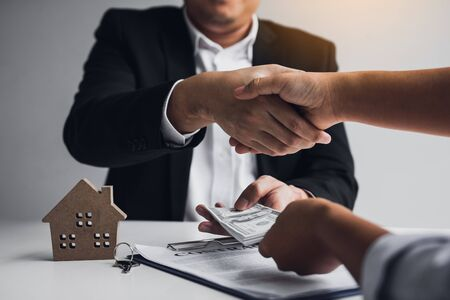 Home sales agents and buyers work on signing new homes and shaking hands. Stock fotó