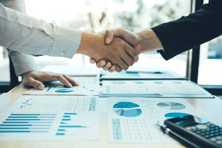 Entrepreneurs collaboration deal shaking hands in a modern office and financial paper graph on desk.