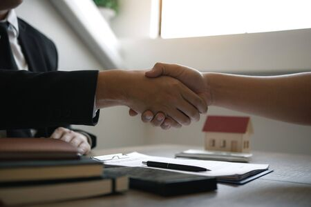 Home sales agents and buyers work on signing new homes and shaking hands. Stockfoto