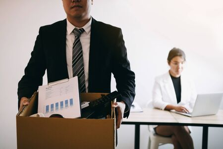 Front view with the male employee standing holding office supplies in the paper box going to submit a resignation letter while a female employee is working behind.