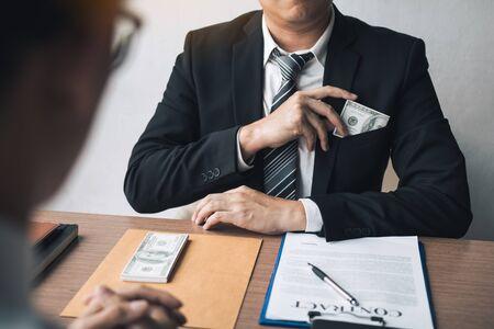Businessman putting stack of money bills in his suit coat pocket. Imagens