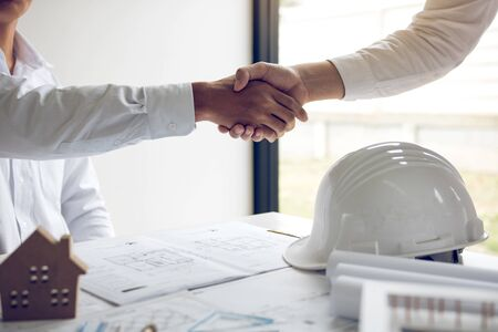 Two partnership engineering man with construction worker greeting shaking hand a foreman at renovating apartment. Stock Photo