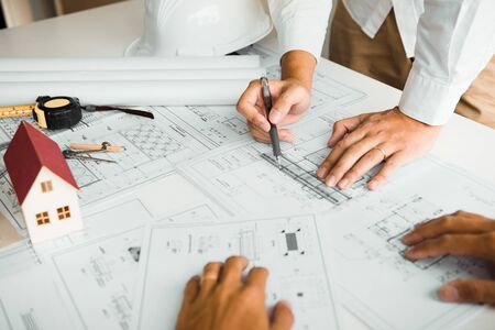 Architects engineer working with blueprints on table and discussing project together at the meeting in the office. Stock Photo