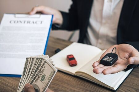 New car buyers are holding cash and handing it to car salespeople while filing a new car signing contract for car buyers.