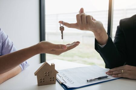 Hand of real estate agent passes the key to new homeowners in office with buyer house concept. 写真素材