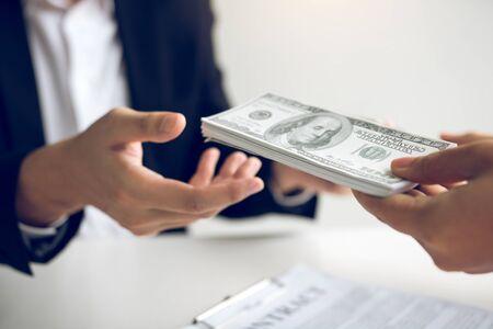 Immobilienmakler und Immobilieninvestoren tauschen mit Anlegern aus, die Bargeld in der Hand des Maklers einreichen.