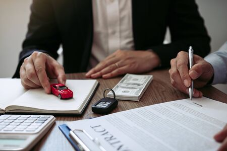 Agent car salesman handed the toy model car to the new car buyer while signing the contract.