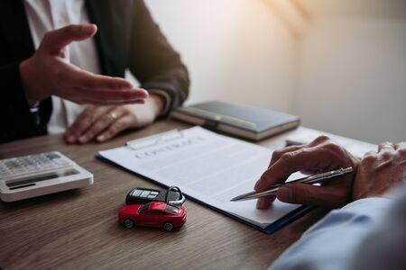 El agente de ventas de automóviles está explicando al comprador del automóvil sobre el contrato de compra del automóvil nuevo y el acuerdo. Foto de archivo