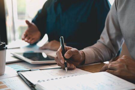 Geschäftspartner von Geschäftspartnern schreiben den Arbeitsfortschritt der Kosten und verwenden ein Tablet, um den Finanzbudgetbericht des Unternehmens zu analysieren und die Zukunft im Büroraum zu planen.