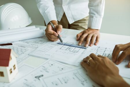 Architects engineer working with blueprints on table and discussing project together at the meeting in the office. Stockfoto